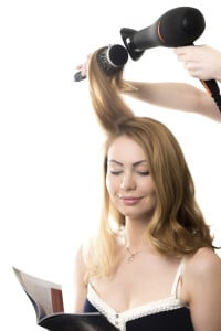 Portrait of young smiling gorgeous blond woman sitting at beauty salon reading fashion magazine, having her hair styled with hairdryer and round hairbrush, studio shot, isolated on white background