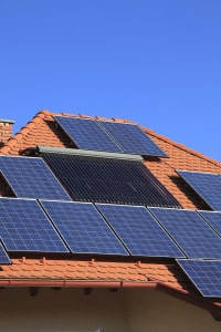 Alternative energy photovoltaic solar panels on tiled house roof